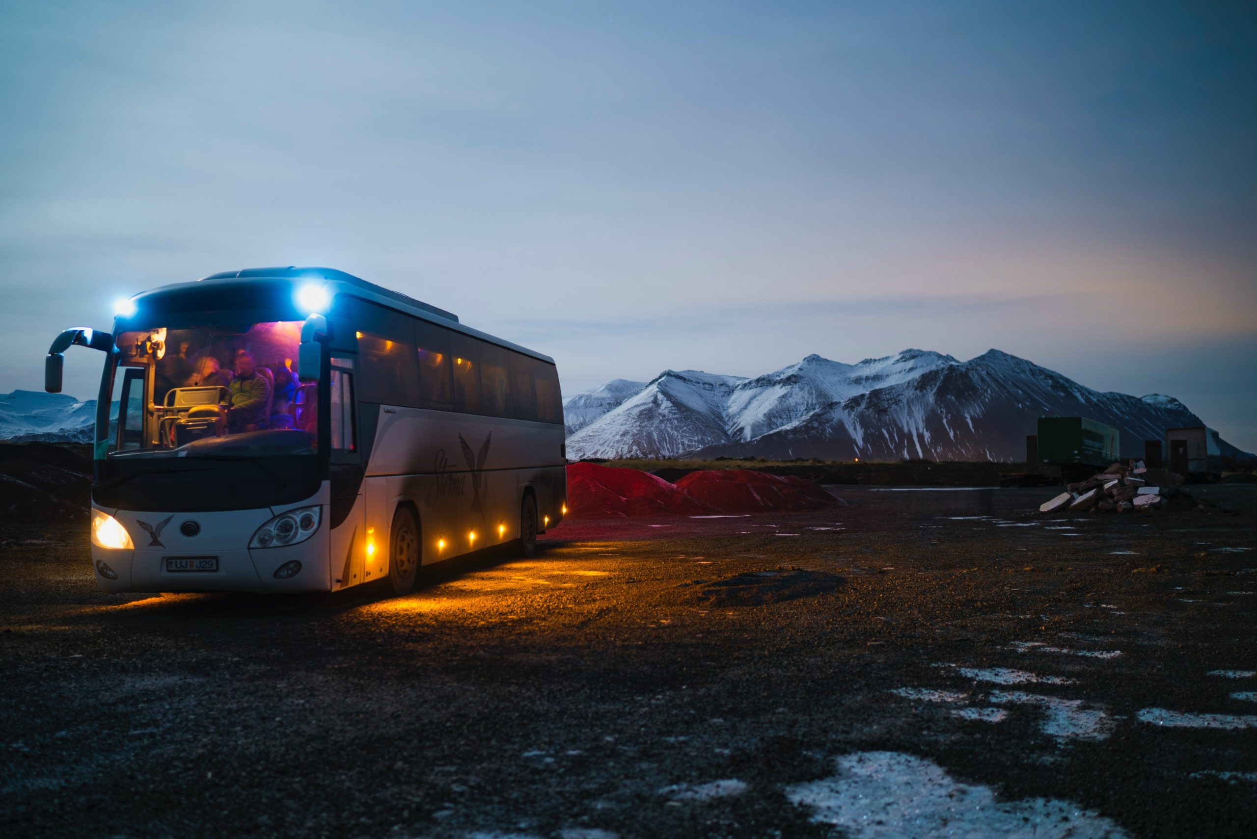 white and black bus running near the mountain